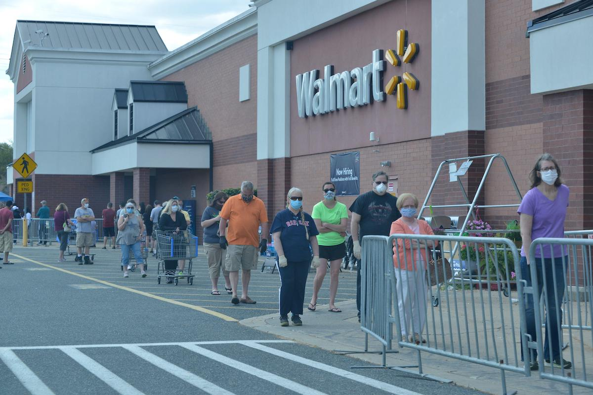 people stand in line outside of a walmart in Massachusetts wearing masks