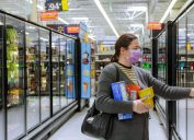 woman wearing mask at walmart while shopping in frozen food aisle
