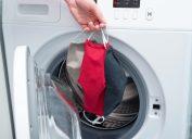 white hand putting three cloth face masks into washing machine