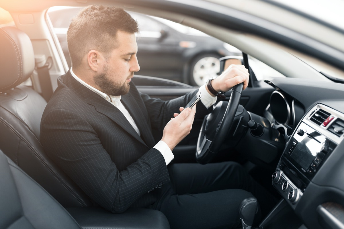 white man in suit looking at phone in car
