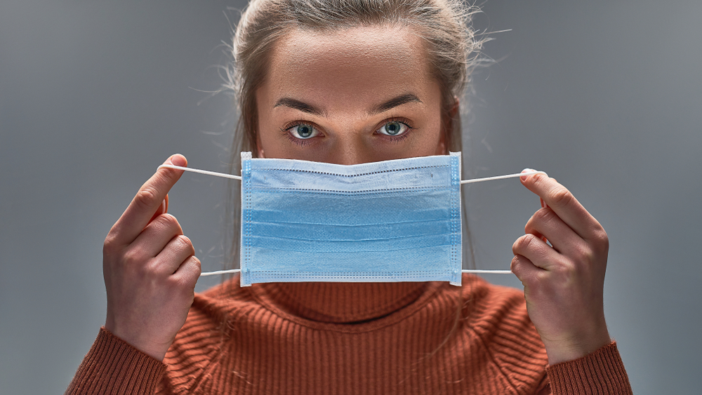 A woman holding a protective face mask over her mouth about to put it on.