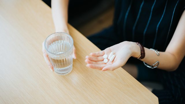 Close up of woman holding a glass of water and medication in her hand