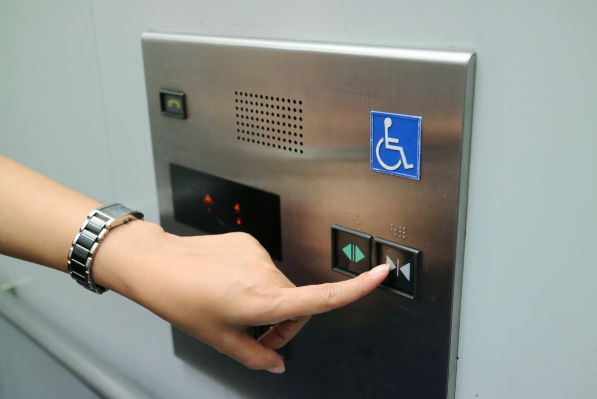 woman's hand pressing elevator button