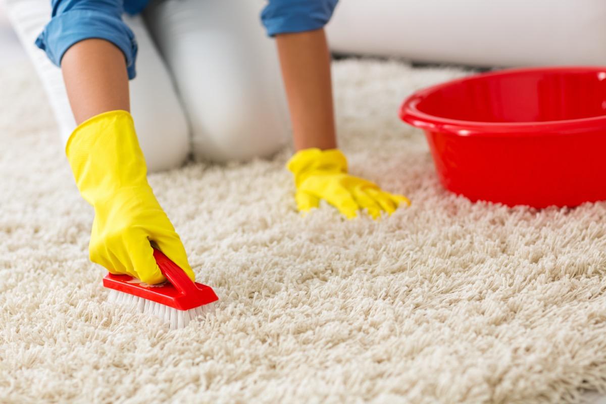woman scrubbing white rug