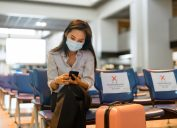 A young woman sitting in an airport while wearing a face mask, sitting next to socially distanced seats