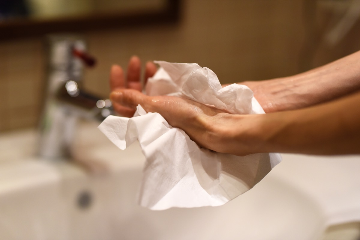 Female hands using paper towel after washing, as a protection against viruses