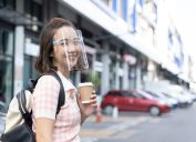 A young Asian woman smiles while wearing a face mask and holding a cup of coffee