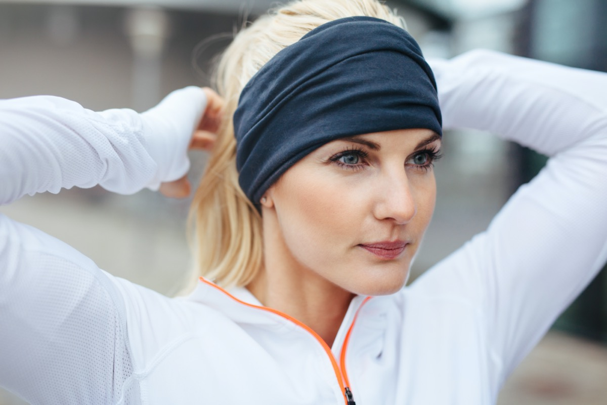 Close-up of young female athlete tying up hair before a run. Sporty fitness woman on outdoor workout looking motivated.