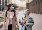 Two friends meet outside on the city street wearing face protective masks to prevent Coronavirus