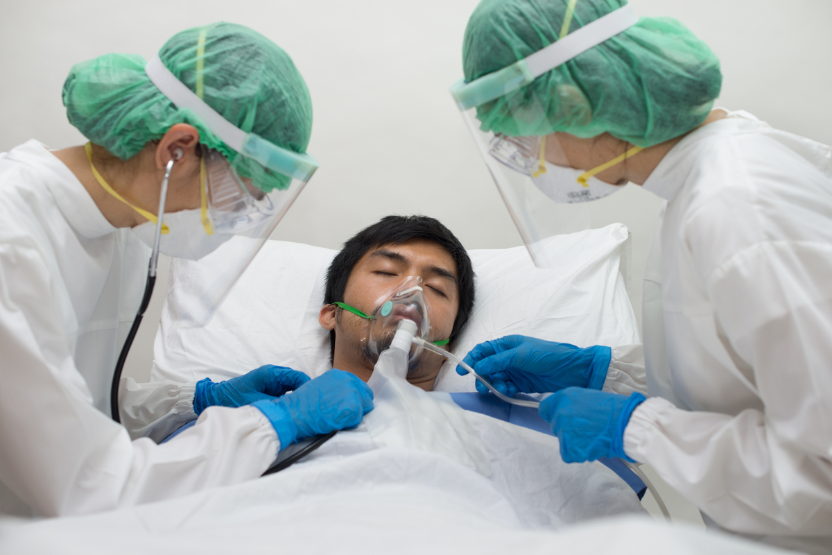 young asian man in hospital with oxygen mask for coronavirus