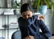 young asian woman coughing or sneezing into her elbow in an office