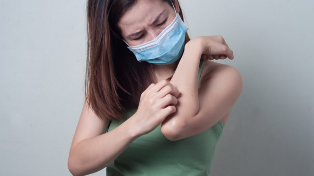 young woman scratching arm while wearing surgical mask