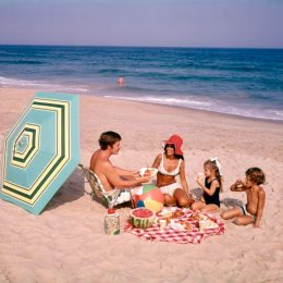 family has a beach picnic in the 1970s