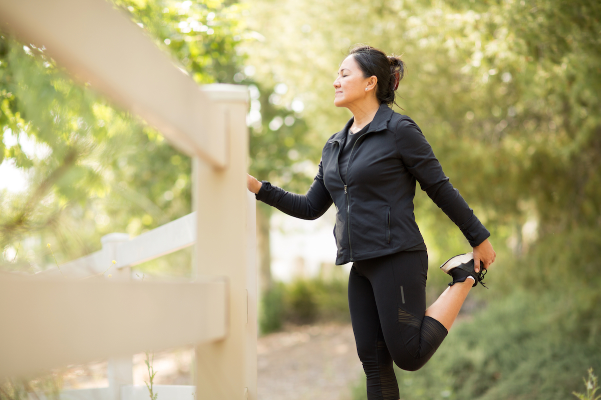 Asian woman stretching before a run