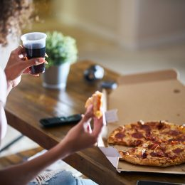 Qoman eating pizza and watching TV