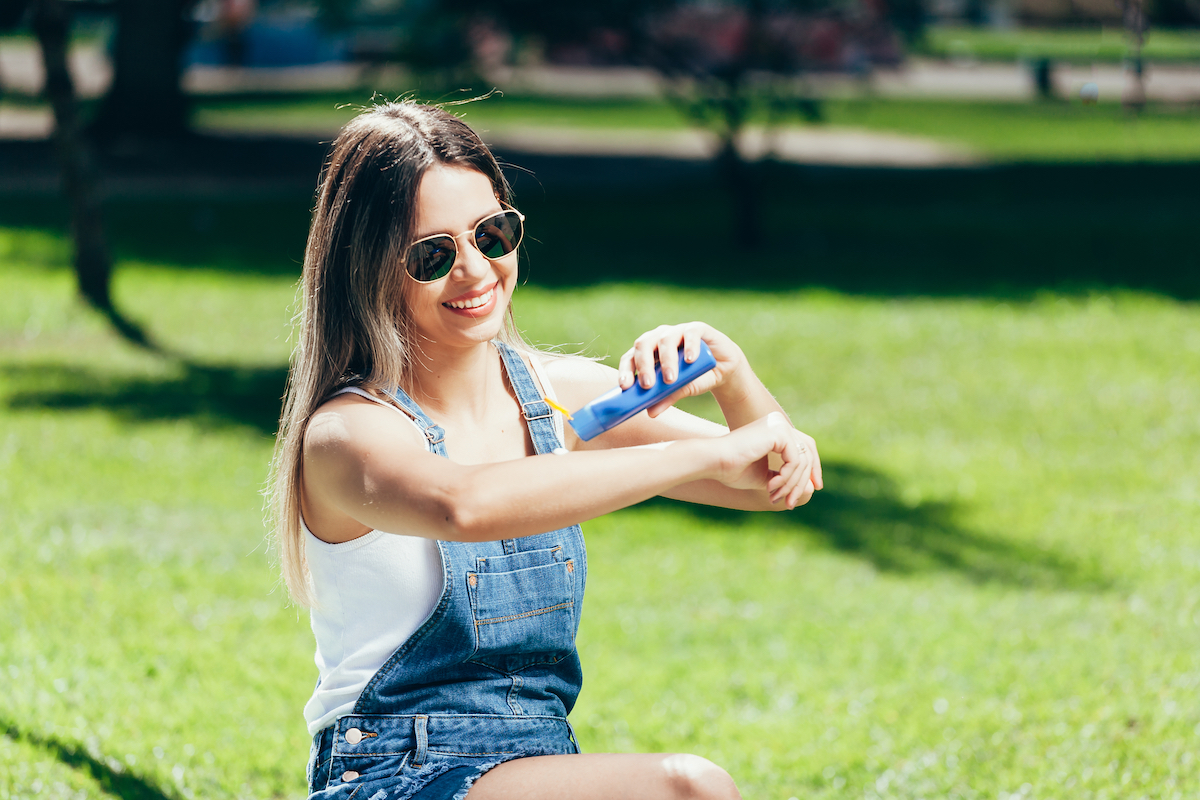 Girl putting on sunscreen in the park