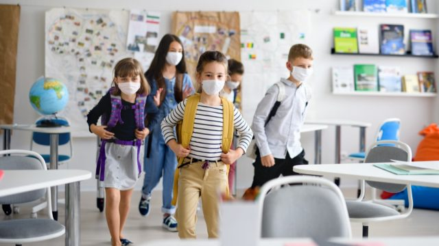 Elementary age school kids at school in mask
