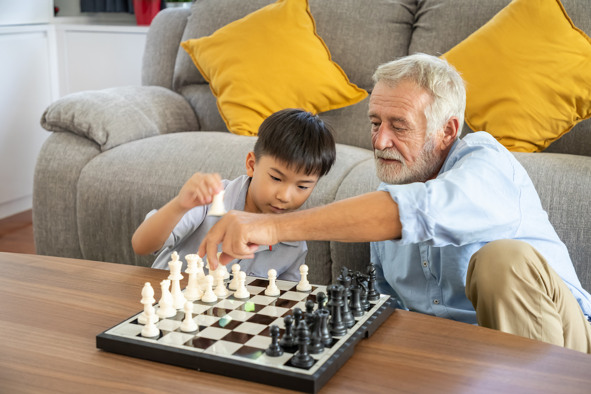 Man playing chess with his grandson