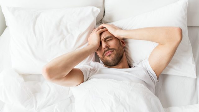Man in bed with headache