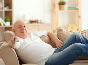 Out of shape older white man watching TV