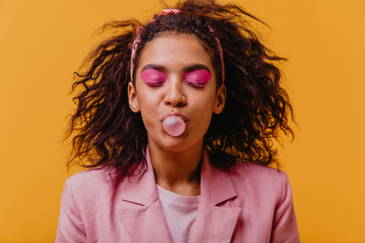 Young black woman blowing bubble with chewing gum
