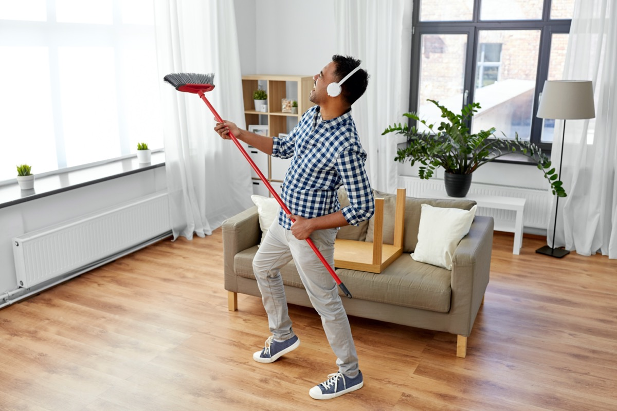 Young man cleaning apartment