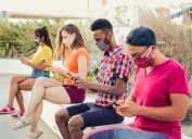 Young people using phones and wearing masks