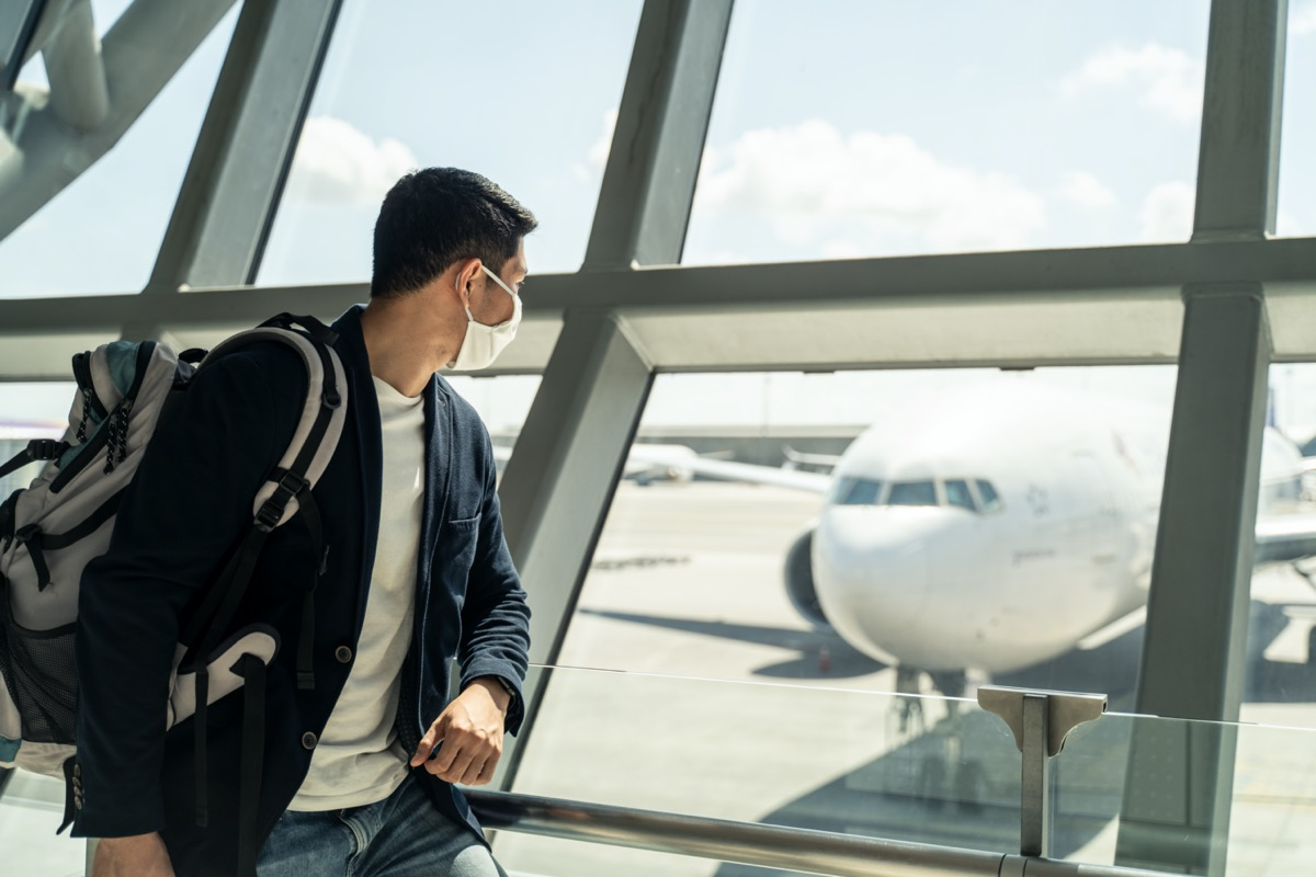 man wears a mask and looks out the airport window at a plane
