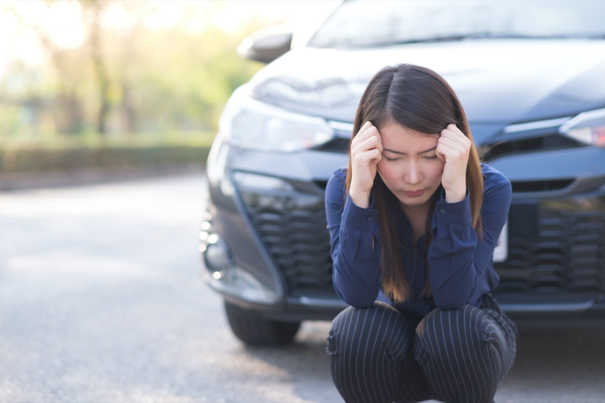 young asian woman upset after car accident