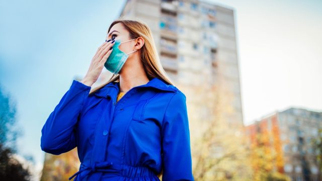 Woman wearing face mask because of air pollution or virus epidemic