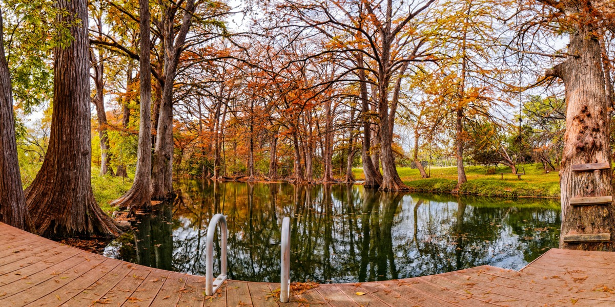 swimming hole with fall foliage around it