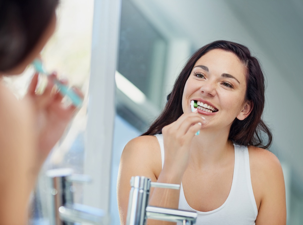Shot of an attractive young woman brushing her teeth in the bathroom at home