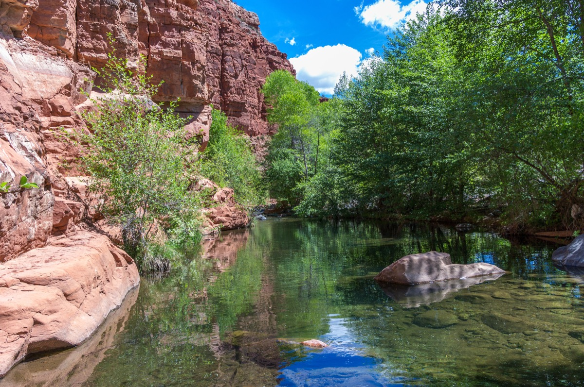 natural swimming hole with sandstone cliff on the left