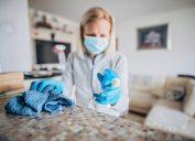 One mature woman cleaning and doing disinfection on all surfaces in her house.