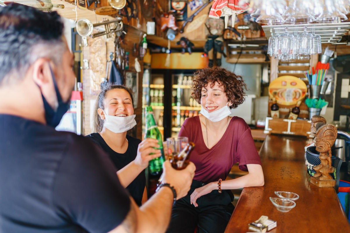 people cheering with beer in bar with illness prevention protection measures are taken