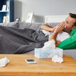 Man with a cold on the couch blowing his nose