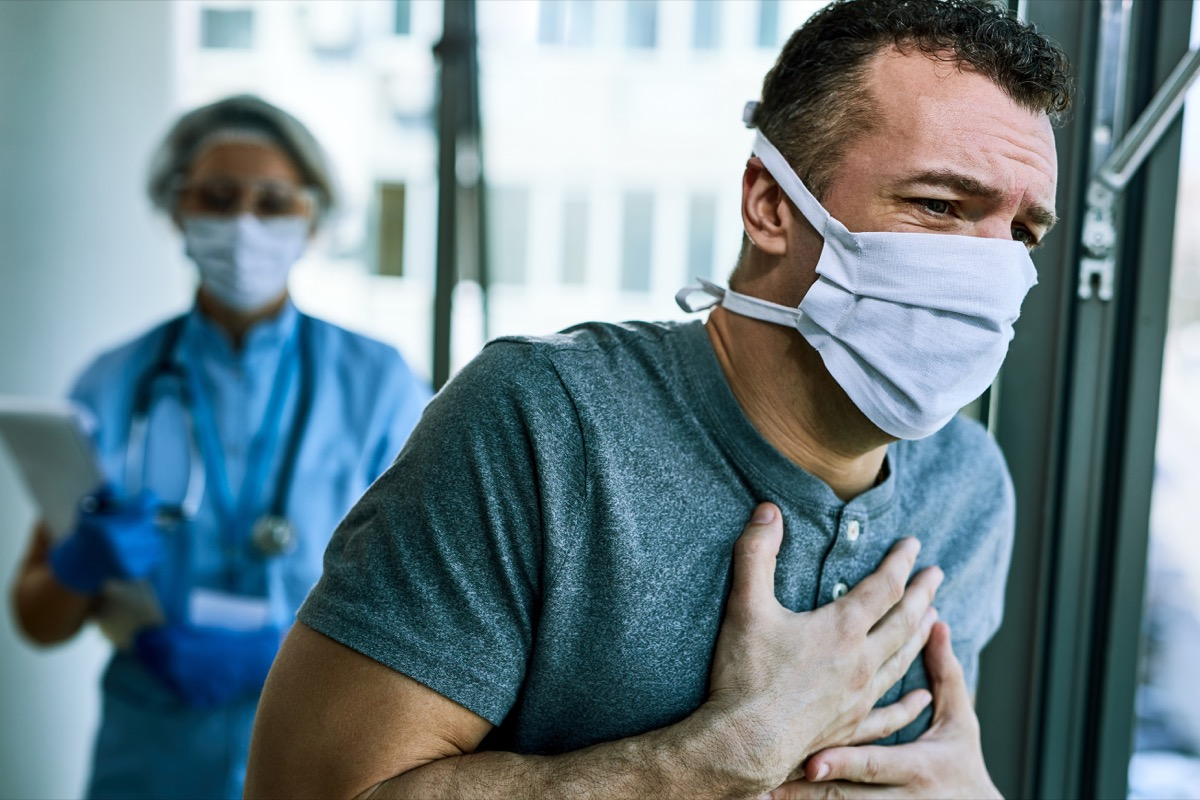 Male patient wearing face mask and feeling chest pain while being at the hospital during coronavirus epidemic. Healthcare worker is in the background.