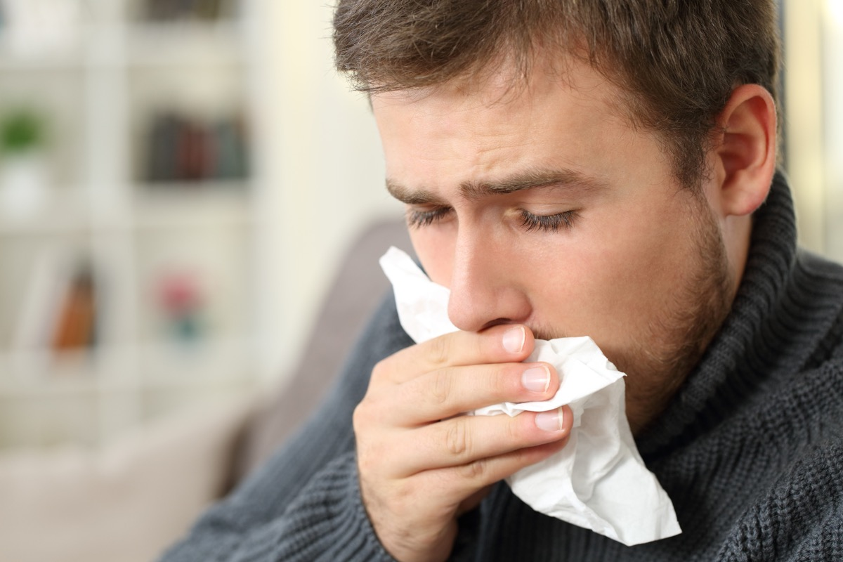 Man with phlegm coughing into tissue at home