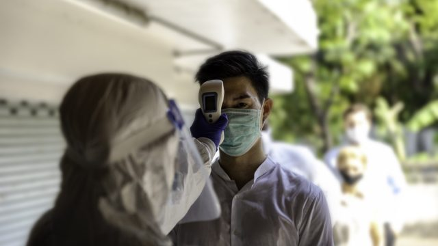 Security guard in PPE suit uses infrared thermometer measuring temperature with a staff scanning for Coronavirus or Covid-19 infection at international office entrance. Medical healthcare