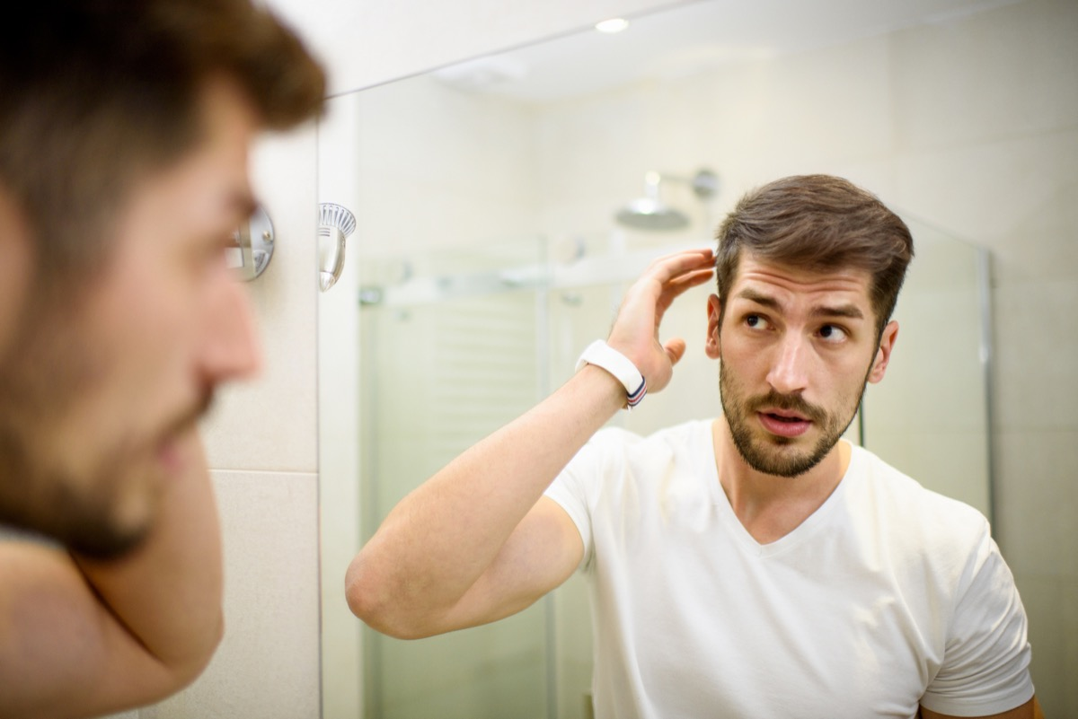 Young man in the bathroom looking in the mirror and fixing his hair with dandruff
