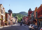 The main street of Deadwood, South Dakota with cars and shops in view.