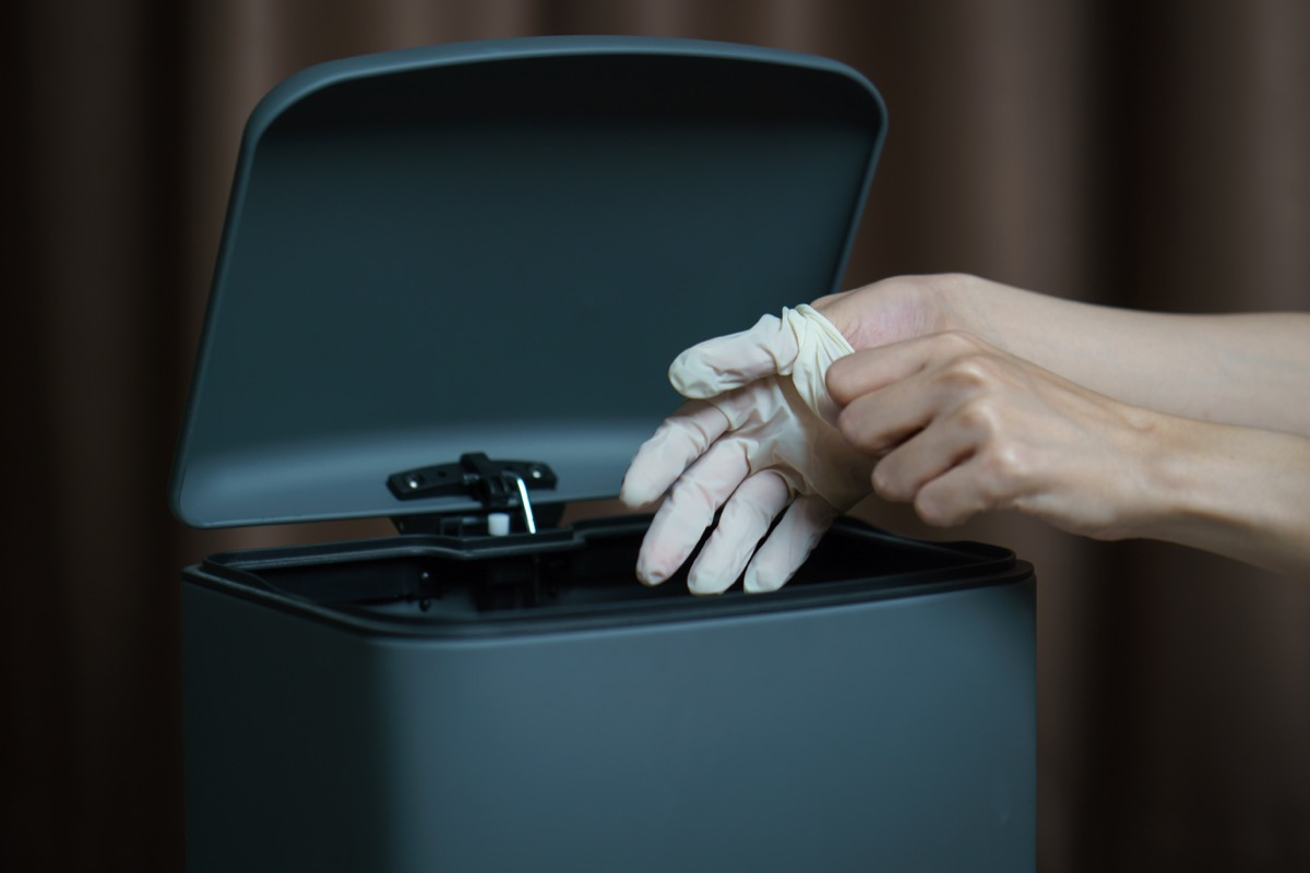 Hand putting used dirty surgical glove to a garbage bin. Mask protect dust and corona virus in trash.