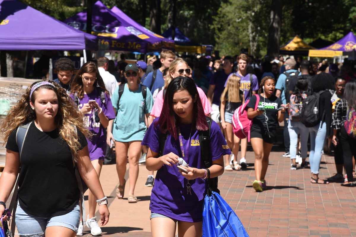 group of students walking outdoors on campus quad in purple clothing
