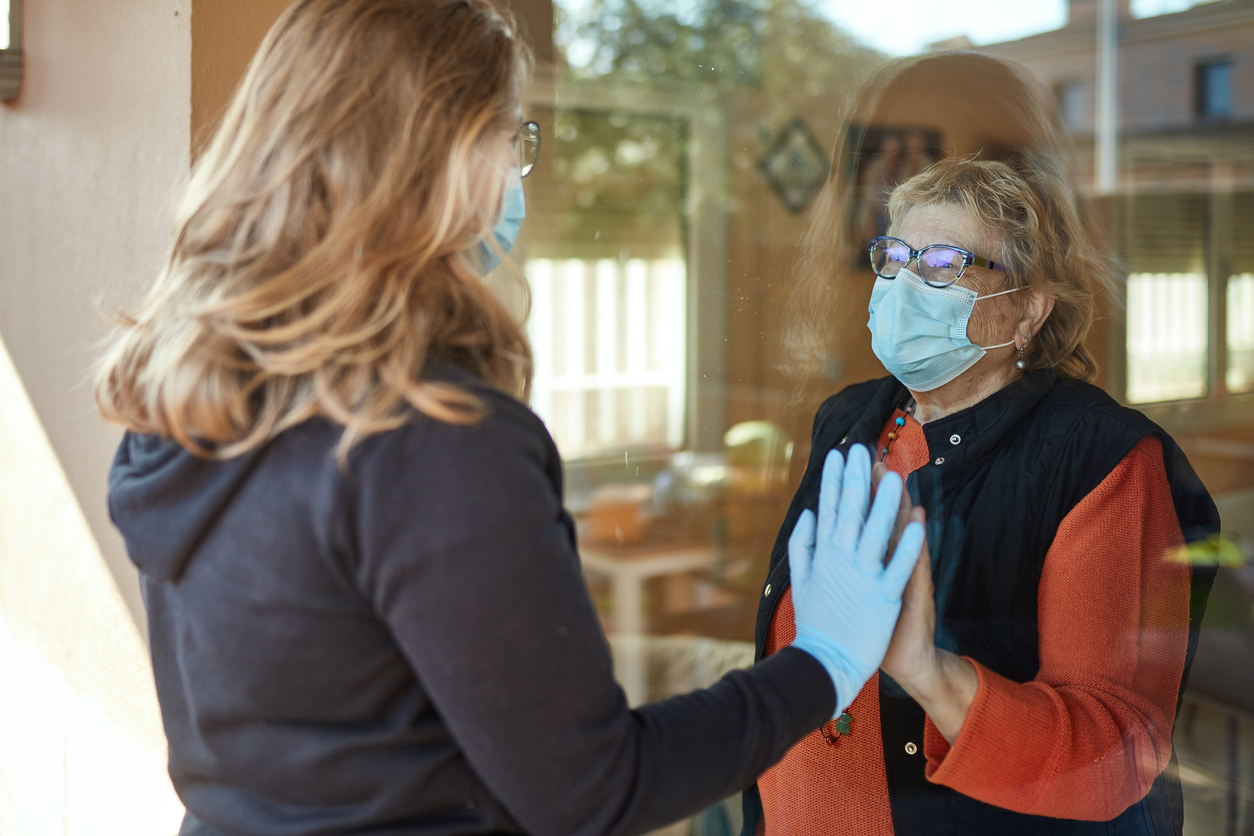 An older woman and her younger relative touch hands through a sliding glass door as they visit during a coronavirus quarantine