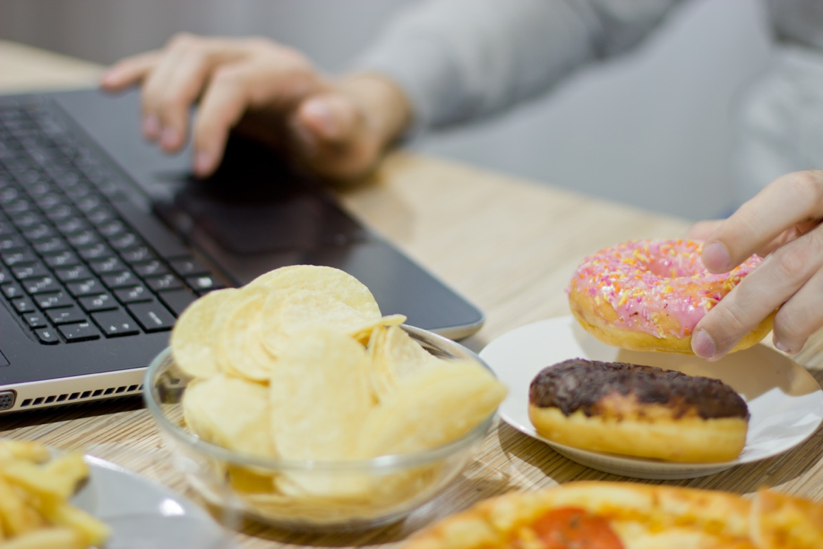 Woman eating donuts and chips while working form home