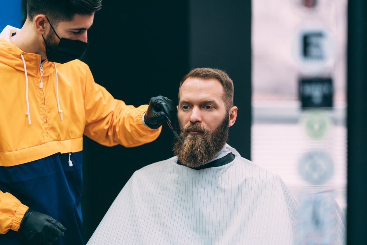 Barber with face mask combing customer's beard