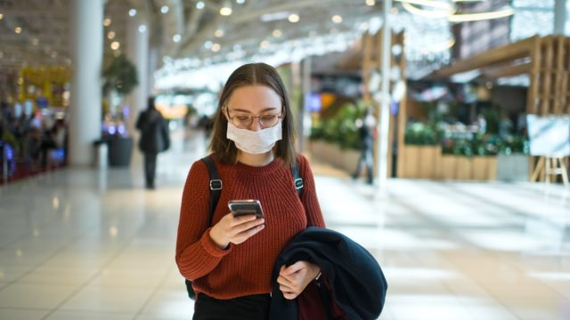 Teenager wearing medical mask protecting herself against virus in a food court of a shopping mall or airport lobby