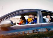 A group of young adults wearing face masks take a ride in a car with the windows rolled down