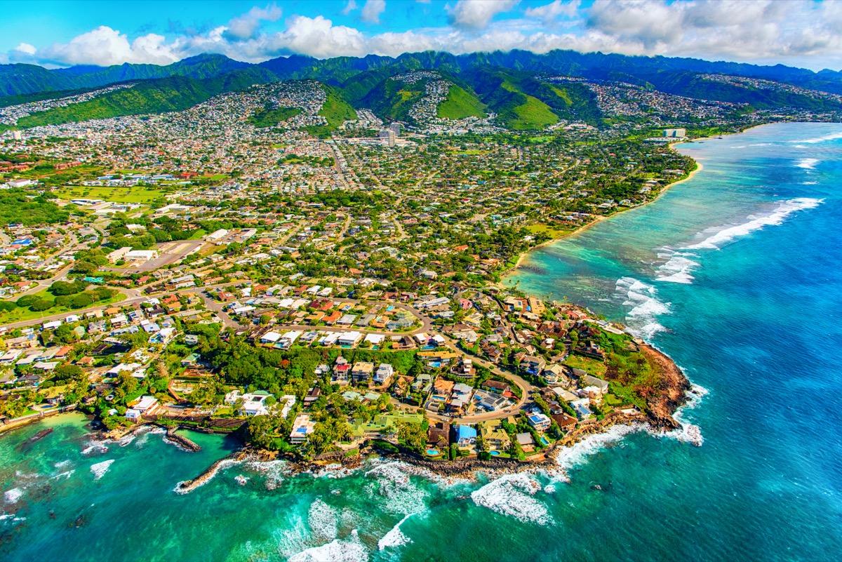 The suburban residential districts of Honolulu, Hawaii along the coastline just outside of downtown from about 1000 feet over the Pacific Ocean.