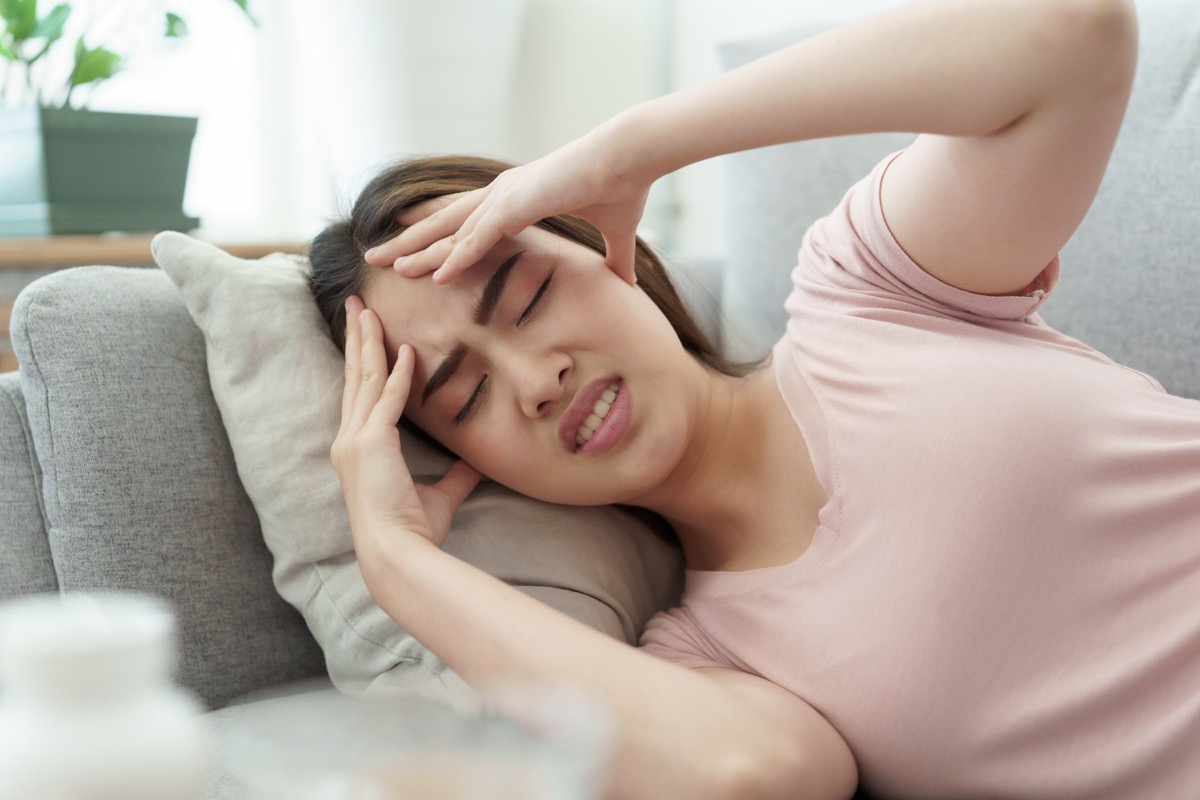 woman with a headache on her couch